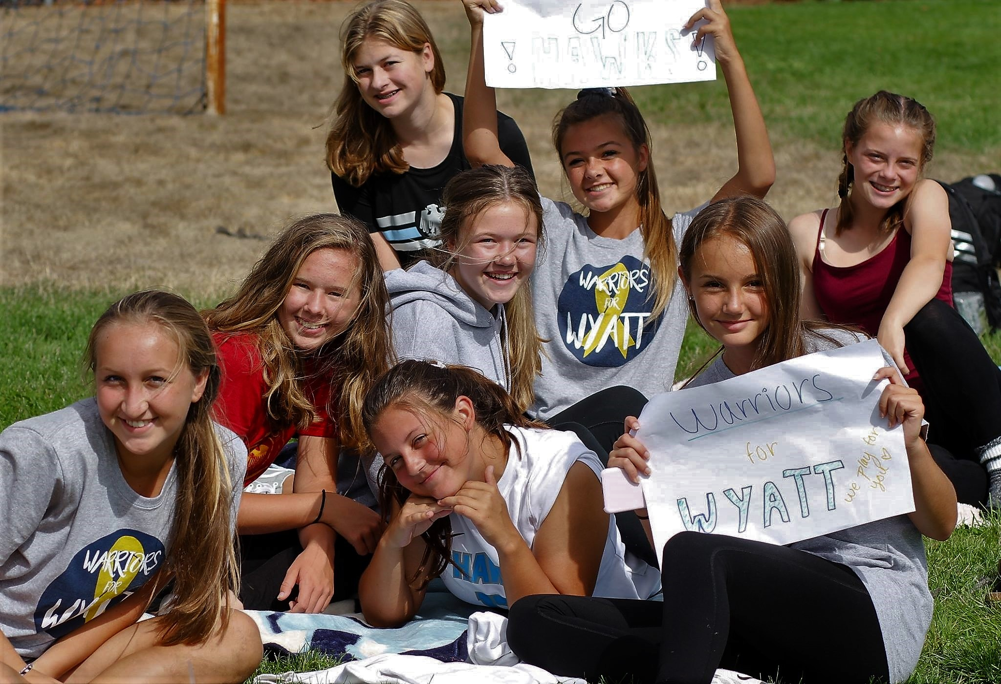Soccer team members hold Warriors for Wyatt signs