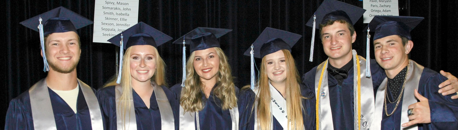 HHS students wearing mortarboards and graduation gowns smile for the camera.